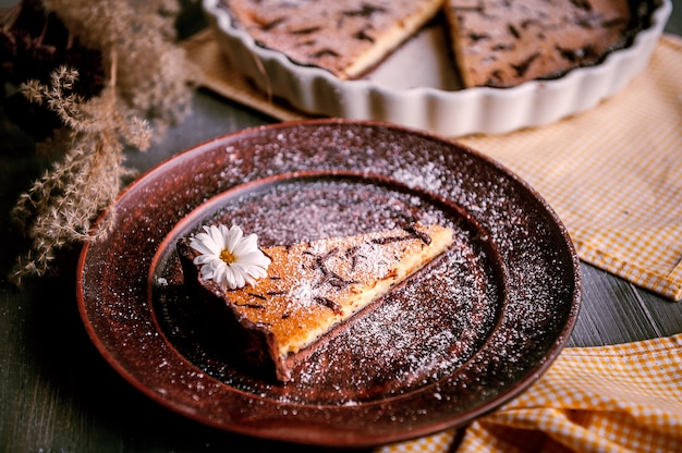 Baked cake in a ceramic form sprinkled with chocolate slices on a wooden table.