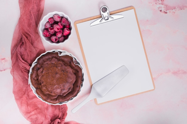 Baked cake; raspberry; spatula on clipboard with white paper over the pink textured background