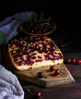 Baked cake with cherries on a brown wooden board