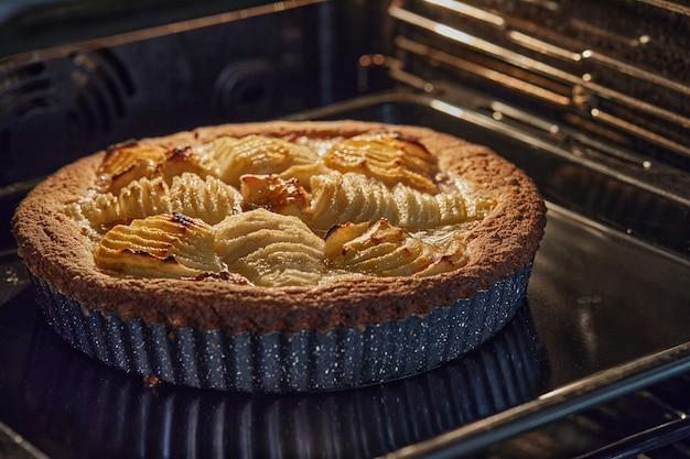 전기 오븐에 금속 형태로 배와 복숭아를 넣은 구운 케이크