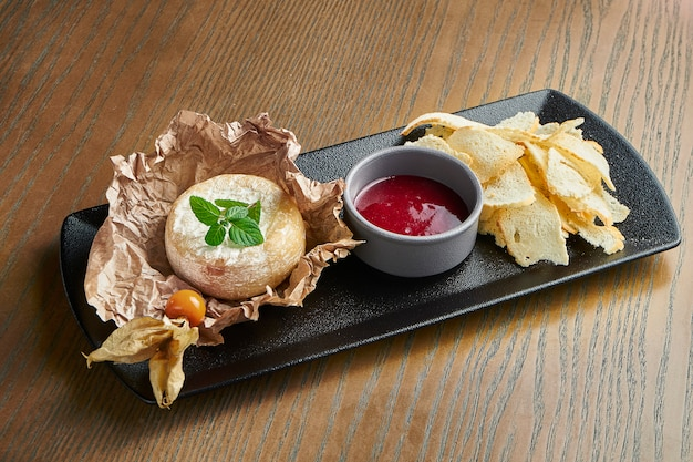 Baked camembert on a black plate on a wooden surface with a croutons and jam.close up view. film effect during post. soft focus