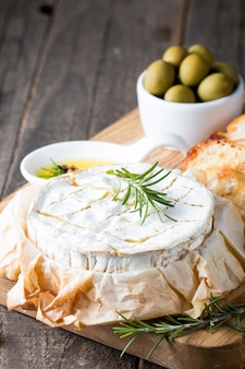 Baked camembert or brie cheese on a wooden board.