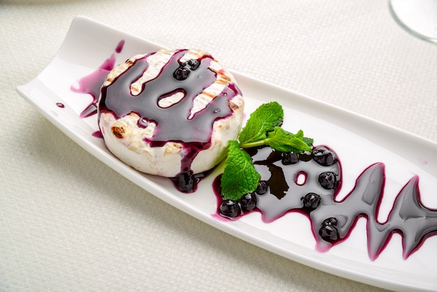 Baked camembert cheese with cranberry sauce and mint