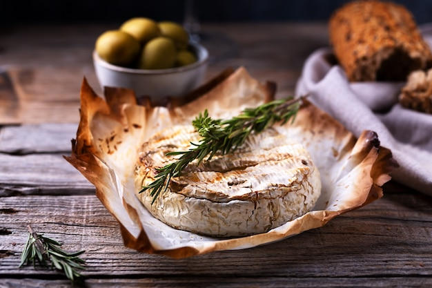 Baked camembert cheese with rosemary, olives and bread, selective focus