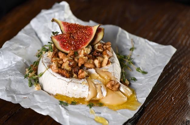 견과류와 꿀, 무화과, 타임 슬라이스로 구운 카망베르. 프리미엄 사진