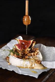 견과류와 꿀, 무화과와 백리향 조각을 곁들인 구운 카망베르. 프리미엄 사진