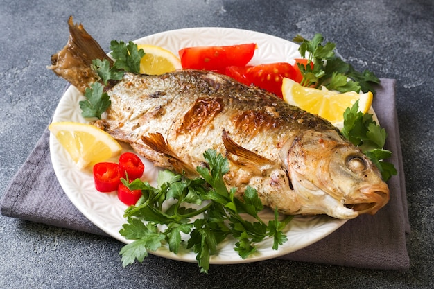 Baked carp fish with vegetables and spices on a plate on a dark table with a copy of space.