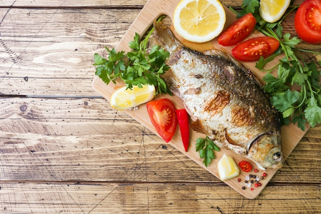 Baked carp fish with vegetables and spices on a wooden table with a copy of the space.