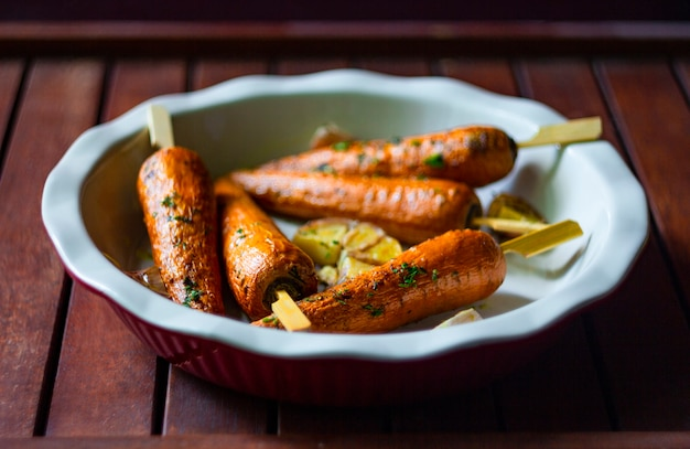 Запеченная морковь в круглой форме для выпечки на деревянных фоне. концепция вегетарианской пищи