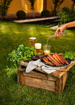 Baked carrots in the oven on the black plate on the wooden box in the garden. woman is pouring bear into the glass with her tattoo hand.