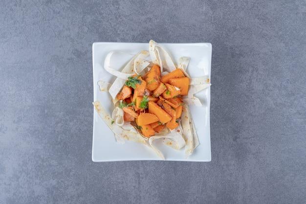 Запеченная морковь с ломтиком лаваша в миске на мраморной поверхности.