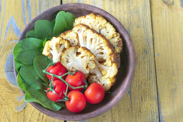 Baked cauliflower with cherry tomatoes and fresh spinach