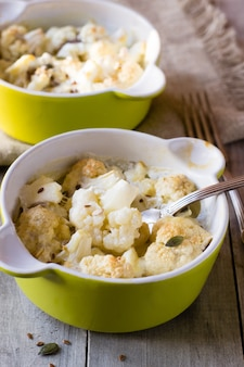 Baked cauliflower with cream on wooden table