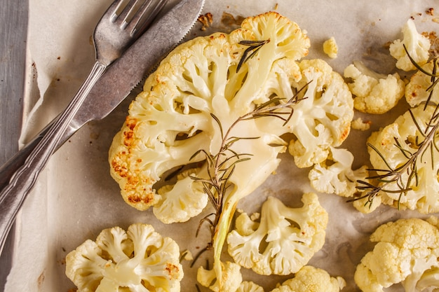 Baked cauliflower with rosemary on the pan, top view.