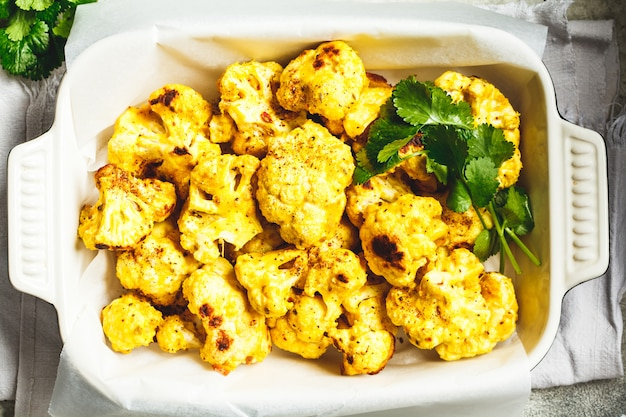 Baked cauliflower with spices and greens in black oven dish.