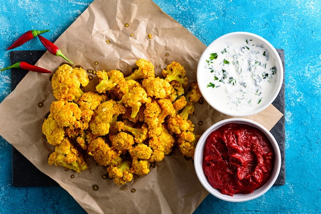 Baked cauliflower with tomato and sour cream sauce on parchment paper on blue background. vegetarian appetizer concept