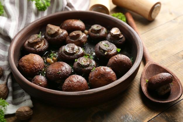 갈색 그릇에 버터, 파슬리, 구운 마늘을 곁들인 구운 샴 피뇽 버섯