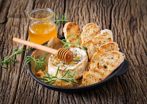 로즈마리와 꿀을 곁들인 구운 치즈 카망베르. 맛있는 음식.