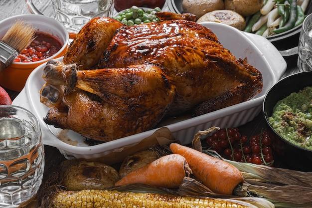 Запеченная курица и запеченная кукуруза. семейный обеденный стол. запеченная курица и овощи с бокалами сидра. вкусный деревенский ужин