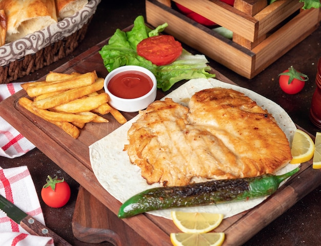 Baked chicken breast with french fries in lavash with vegetables and ketchup on wooden board