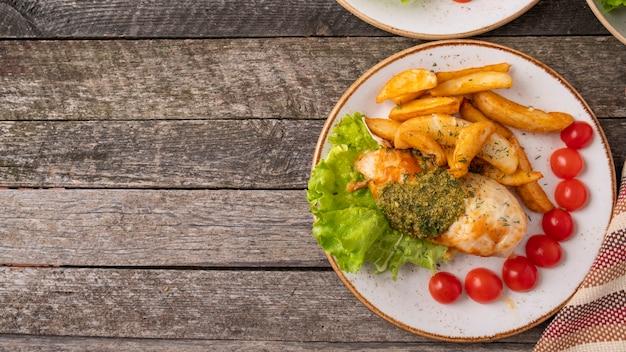 Запеченная куриная грудка с соусом песто и свежими помидорами черри на тарелке