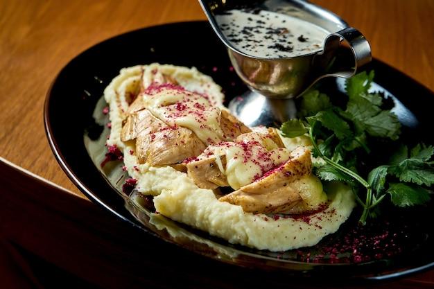 Запеченная куриная грудка с сыром сулугуни и картофельным пюре подается в черной тарелке. еда в ресторане