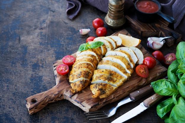 Запеченные куриные грудки на деревянной доске с овощами, выборочный фокус, копией пространства