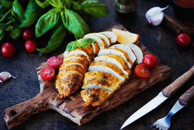 Запеченные куриные грудки на деревянной доске с овощами, выборочный фокус