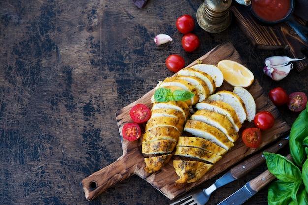 Запеченные куриные грудки на деревянной доске с овощами, вид сверху, копией пространства