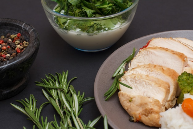 Запеченные куриные грудки или филе на тарелке, розмарин, миски с соусом и ягодами душистого перца на черном фоне. вид сверху.