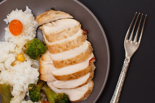 Запеченные куриные грудки или филе с рисом, овощами и зеленью на тарелке с вилкой. вид сверху.