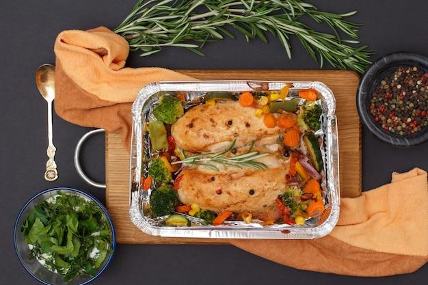 木製のまな板とキッチンナプキンの金属容器に野菜と野菜を入れた焼き鶏の胸肉または切り身。ソース、スプーン、ローズマリー、スパイスが入ったガラスのボウル。上面図。