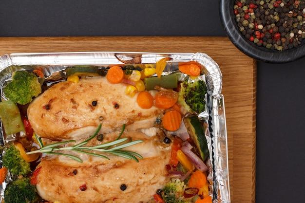 Запеченные куриные грудки или филе с овощами и зеленью в металлическом контейнере на деревянной разделочной доске. стеклянная миска с душистым перцем. вид сверху.