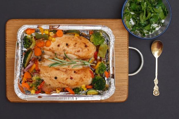 木製のまな板の金属容器に焼き鶏の胸肉または野菜と野菜の切り身。ソースと金属のスプーンが付いているガラスのボウル。上面図。