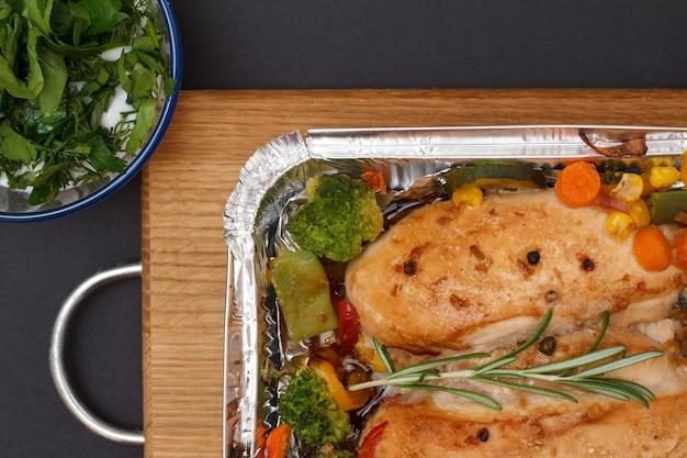 Запеченные куриные грудки или филе с овощами и зеленью в металлическом контейнере на деревянной разделочной доске. стеклянная миска с соусом и розмарином. вид сверху.