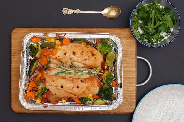 木製のまな板の金属容器に焼き鶏の胸肉または野菜と野菜の切り身。ソースとスプーン、磁器プレートとガラスのボウル。上面図。