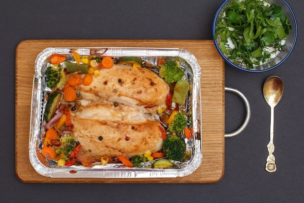 木製のまな板の金属容器に焼き鶏の胸肉または野菜と野菜の切り身。ソースとスプーンでガラスのボウル。上面図。