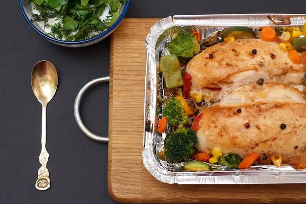 Запеченные куриные грудки или филе с овощами и зеленью в металлическом контейнере на деревянной разделочной доске. стеклянная миска с соусом и ложкой. вид сверху.