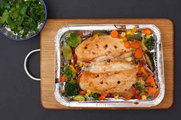 Запеченные куриные грудки или филе с овощами и зеленью в металлическом контейнере на деревянной разделочной доске. стеклянная миска с соусом в углу .. вид сверху.