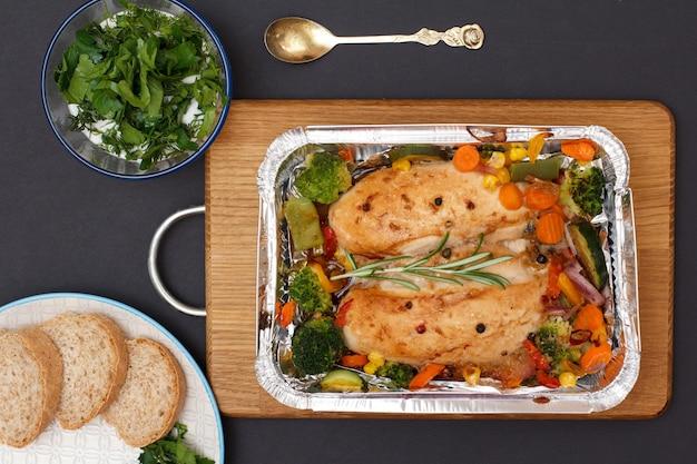 Запеченные куриные грудки или филе с овощами и зеленью в металлическом контейнере на деревянной разделочной доске. стеклянная миска с соусом, тарелка с хлебом и ложкой. вид сверху.