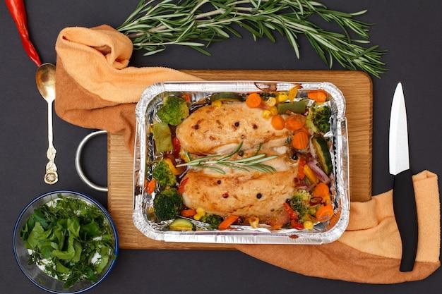 Запеченные куриные грудки или филе с овощами и зеленью в металлическом контейнере на деревянной разделочной доске. стеклянная миска с соусом, ложкой и ножом. вид сверху.
