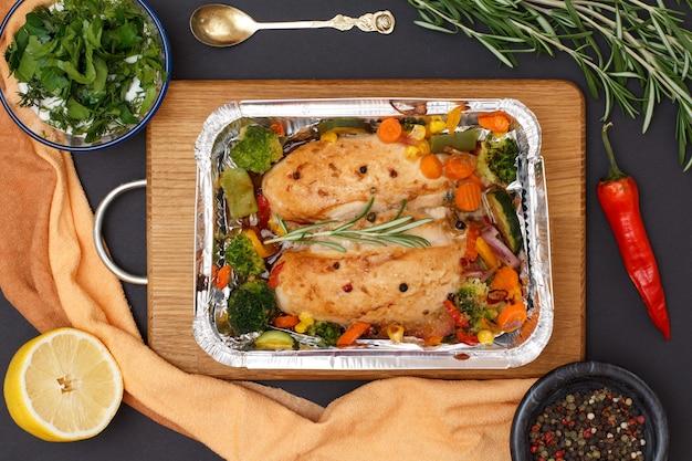 Запеченные куриные грудки или филе с овощами и зеленью в металлическом контейнере на деревянной разделочной доске. стеклянная миска с соусом, ложкой и специями. вид сверху.