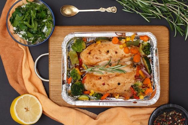木製のまな板の金属容器に焼き鶏の胸肉または野菜と野菜の切り身。ソース、スプーン、レモン、スパイスが入ったガラスのボウル。上面図。