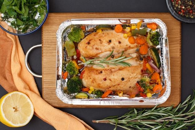 Запеченные куриные грудки или филе с овощами и зеленью в металлическом контейнере на деревянной разделочной доске. стеклянные пиалы с соусом и душистым перцем, лимоном. вид сверху.