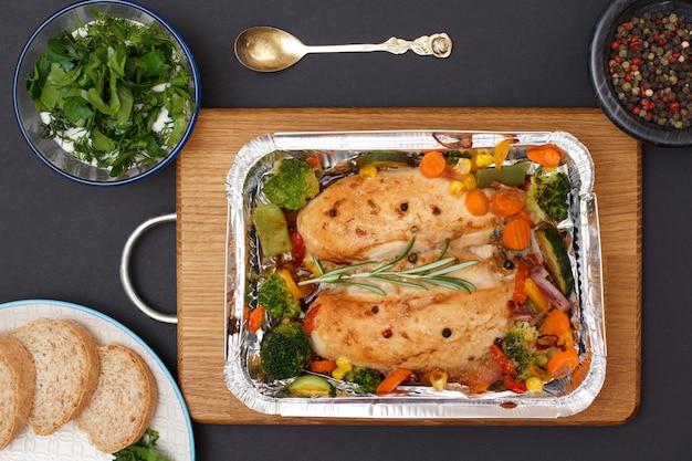 Запеченные куриные грудки или филе с овощами и зеленью в металлическом контейнере на деревянной разделочной доске. стеклянные миски с соусом и душистым перцем, тарелка с хлебом. вид сверху.