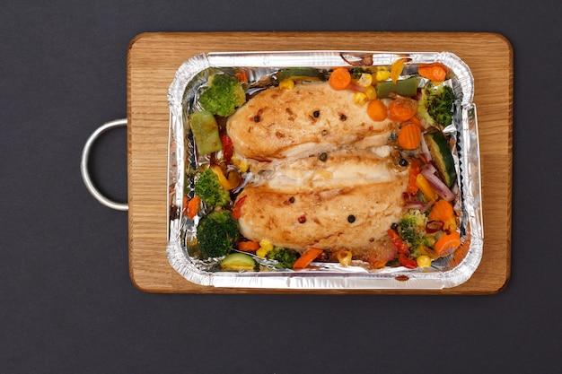 Запеченные куриные грудки или филе с овощами и зеленью в металлическом контейнере на деревянной разделочной доске. вид сверху.