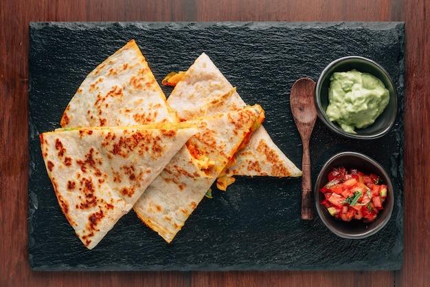 ฺbaked chicken and cheese quesadillas served with salsa and guacamole on stone plate.