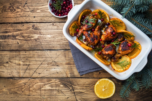 Baked chicken drumstick with oranges and cranberries in a baking sheet on a wooden background. christmas food table with decorations. copy space.