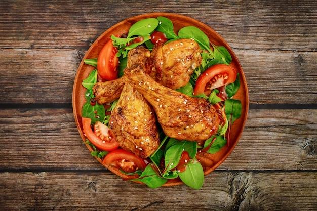 소박한 나무 배경에 샐러드와 구운 된 치킨 나지만 닫습니다. 평면도.