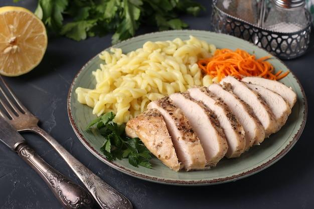 Запеченное куриное филе, паста и свежая морковь - вкусный и полезный завтрак. крупный план